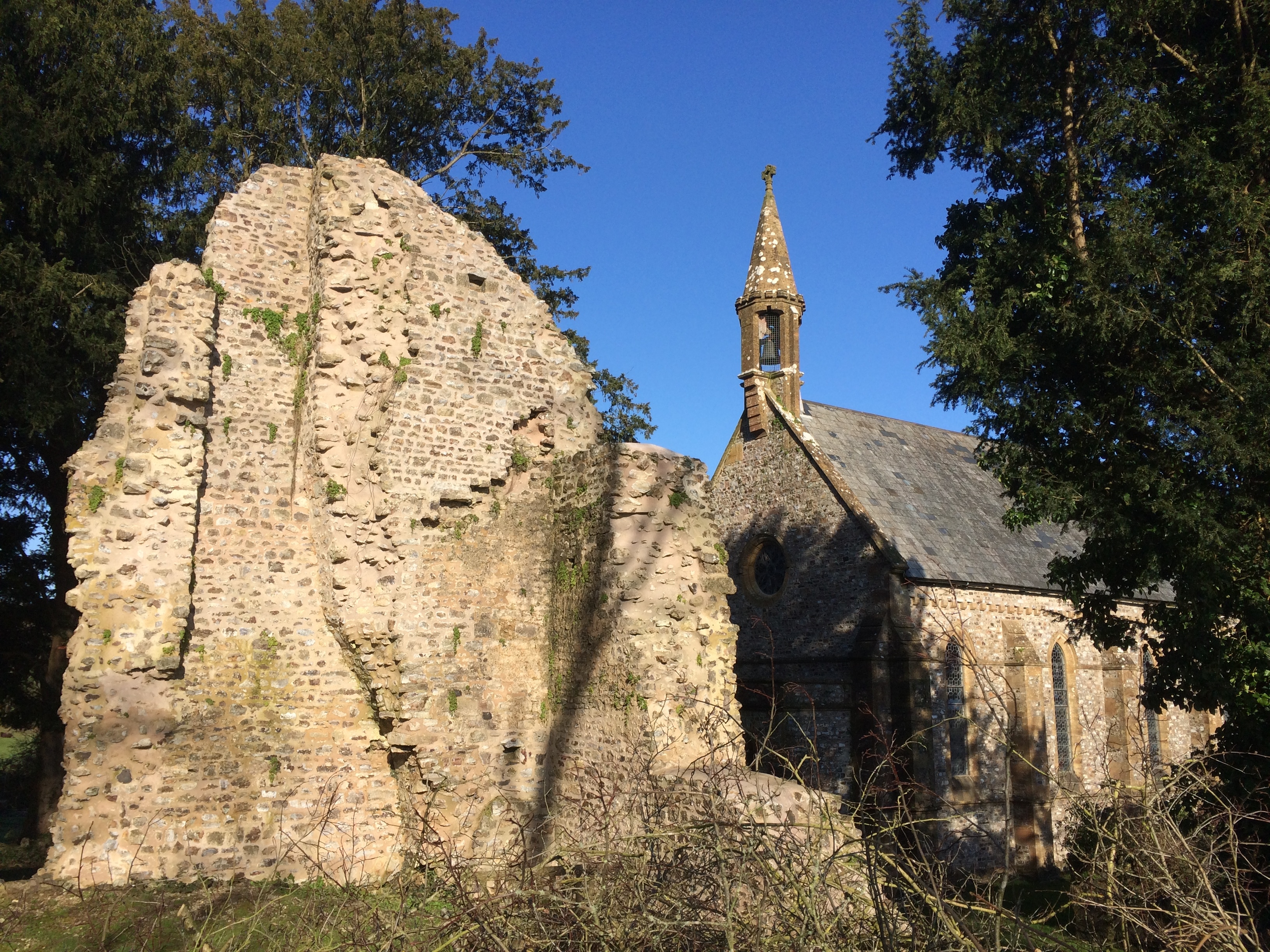Ruins of the west range of Dunkeswell Abbey with the Victorian Church behind
